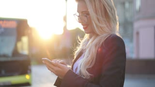 Gorgeous blonde woman in formal look with red lipstick, in glasses standing on the bus stop, actively using her phone, and reacting happily, smiling. Being online, social networks. Modern lifestyle.