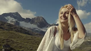 Gorgeous blondie is smiling to the sunshine, while walking in the mountains. Attractive girl smiles.