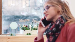 Gorgeous European girl gladly answering the phone call, then looks through the window and putting down the phone. Modern communication, portable devices. Technology. Comfortable café's interior.