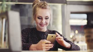 Gorgeous lady with natural makeup using her mobile phone. Modern devices. Being online, active lifestyle. Businesswoman in the café.