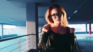Gorgeous sexy blonde girl walks down the parking, and looks seductively right towards the camera, emotionally corrects her leather jacket and eyeglasses. Hot nerdy girl. Natural beauty.