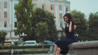Gorgeous young brunette woman in a long casual black dress sits on the fountain and actively uses her phone for chatting. Romantic atmosphere, flirting online. Dreamy mood, cheerful emotions.