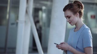 Gorgeous young woman passing by the airport entrance and using her phone, gladly texting back. Charming smile, female beauty. Modern communication, contemporary style