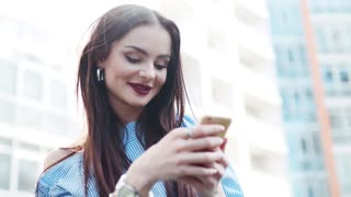 Gorgeous young woman uses her phone and happily smiling. Stylish look, red lips, nose piercing. Being happy. Social networks, being online. Modern culture. Searching for love.