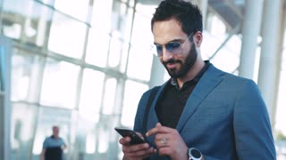 Handsome bearded Eastern businessman standing by the airport entrance, using his phone and smiles happily to received message, texts back. Stylish suit, sunglasses, elite watch.