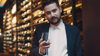 Handsome bearded man in a black suit cheers with the glass of wine. Shelves with wine on the background. Good looking bachelor, male portrait. Celebration time, being happy.