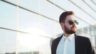 Handsome bearded man in a sunglasses passing by the airport terminal, answers the phone call, looks around, nodes. Business trip, business meeting.