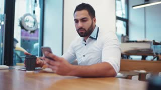 Handsome bearded man in a white formal shirt is using his phone for the internet surfing while drinking coffee. Modern life, businessman. Smartphone, social networks.