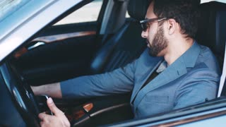Handsome bearded man in stylish sunglasses sits in the business class car holding the phone, gets the message, smiles happily and respond to it. Successful lifestyle, luxurious look, corporate style.