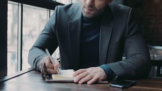 Handsome businessman in a formal outfit sits in the café and signs papers then looks right towards the camera. Active lifestyle, business lunch. Male portrait. Urban café interior on the background.