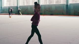 Little girl has a training in the sport school, she stretches, splits, whirls and performs amazing ballet dance. Hobby, talented kids. New generation, modern kids.