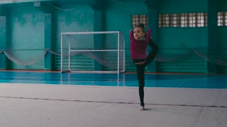 Little girl practices gymnastics in a sport school, she stretches, splits standing on one leg, whirls. Ballet school, professional dance. Cheerful mood, sport motivation. Having fun, favorite activity