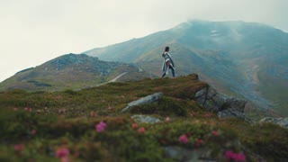 Lone European girl in poncho walks down the moist mountain hills. Hills covered with violet flowers, no people around. Adventure, volcano, pure nature, enjoying the landscape. Slow motion