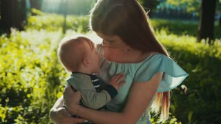 Long-haired mommy hugs tightly her little smiling baby boy while sitting under the tree in park, in bright sunlight. Cuteness, love, happy together, family bounds. Family portrait
