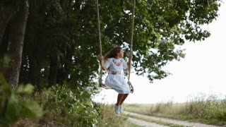 Lovable little girl in a white embroidered dress enjoying the free time, swaying on a wooden swing seat in a garden. Positive emotion, happy childhood. Slow motion