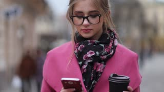 Lovely girl in a trendy look, standing in the city-center having a cup of coffee and texting message. Being busy. City lights on the background. Being online, virtual reality. Modern lifestyle.
