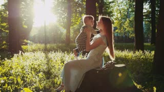 Lovely young mother with long hair sits on a tree stump in a bright sunlight and plays with her son. Having fun, happy childhood. Family portrait, sun lens