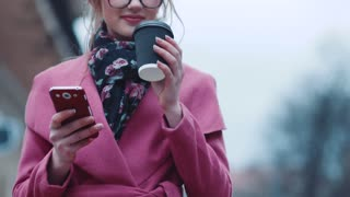 Lovely young woman drinking a cup of hot coffee and using her cell phone for texting. Busy lifestyle. Female portrait.