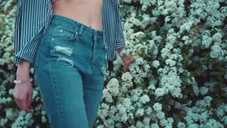 Low angle shot of a hot fit woman in trendy high-waist jeans walking down the garden of blooming flowers, touching the blossom. Beautiful landscape, active lifestyle, healthy living. Female portrait