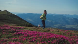 Low angle shot of stylish female tourist running down the flowered mountain hill. Close up view of pink mountain lavender under the strong wind, pure nature. Active lifestyle, cheerful mood.