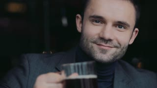 Male portrait of a handsome man in a formal wear raising a beer mug in a toast and drinking cyber gladly. Portrait. Having fun, little party.