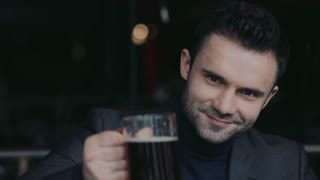 Male portrait of a handsome man in a formal wear toasting with a beer mug and drinking cyber gladly. Having fun, little party.
