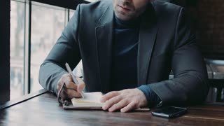 Male portrait of a serious businessman signing documents in the café. Formal outfit, active lifestyle. Successful life.