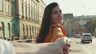 Man follows cheerful attractive smiling young woman leading him to the center of old town. Follow me concept, trust, adventure time. Having fun, positive emotions, joyful mood.