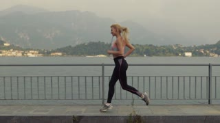 Morning jogging by the sea shore, amazing girl in the sportswear. Just do it. Slow motion.