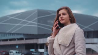 Portrait of a young beautiful girl talking on her phone with a partner whilst standing in front of a modern big building.