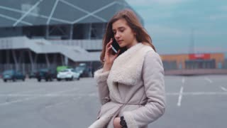 Portrait of a young nice lady talking on her phone standing in front of a modern business building in the cloudy weather.
