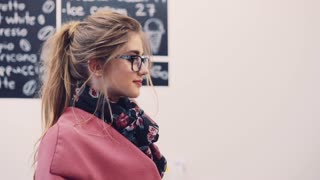 Pretty blonde girl with casual hairstyle and stylish glasses standing by the coffee bar waiting for her order, receives her coffee and gives a bright thankful smile. Cozy café atmosphere.