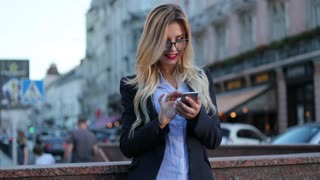 Pretty blonde woman in a business suit with red lips standing by the underground passage, and actively using her phone for texting, reacting happily, smiling brightly, texting back, stroking her hair.
