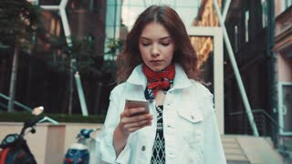 Pretty curly woman in a white jeans jacket walks down the city street in a hurry, actively uses her phone. Urban style, trendy outfit, modern communication, digital era. Messaging, being online.