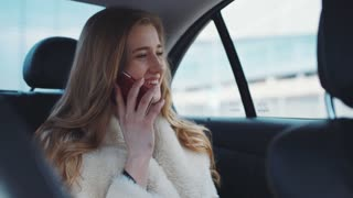 Pretty nice blonde girl talking with friend on her phone and smiling driving home in a modern car of her.