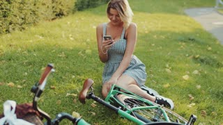 Pretty young blonde woman in a stylish white dress and trendy snickers sits on the lawn in the city park by the green vintage bicycle and actively using her phone. The internet user, being online.