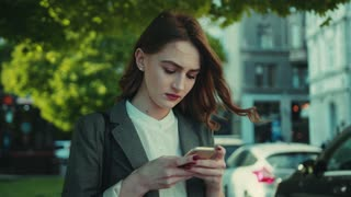 Pretty young woman in a stylish outfit with sad look uses her smartphone. Outside shooting, disappointed look. Negative emotions, bad mood. Strong wind. Being online, female portrait