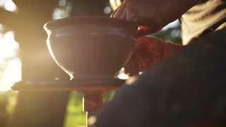 Professional male potter shaping vessel with special tool outside the pottery workshop, studio on the fresh air, in bright sunlight. Crafting process, talent. Hobby, craft. Slow motion