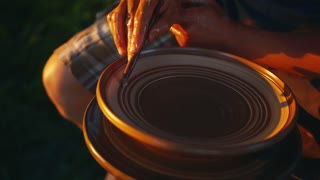 Professional potter decorates the newly finished pottery plate with white paint. Manual work, handcraft. Art, modern times, traditions. Slow motion, camera stabilizer shot, extreme close up