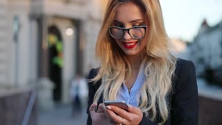 Rotation close up view of a gorgeous blonde woman in a formal wear and glasses standing in the crowded city street and using her phone for texting, gets the message, smiles happily, texts back.