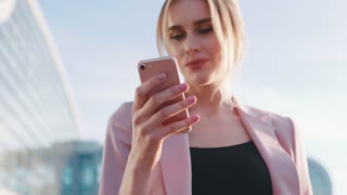 Rotation view of a lovely blonde woman in a pink jacket using her cell phone for texting in a bright sunshine. Outside shooting, sunny weather. Stylish look, smiling. Positive mood.
