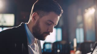 Rotation view of a stylish bearded hipster passionately playing the vintage piano. Professional musician, young pianist. Old-fashioned restaurant interior.