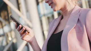 Rotation view of a young blonde business lady smiling and using her phone in a bright sunshine. Modern technologies, being happy. Slow motion, camera stabilizer shot, female portrait, sun lens.