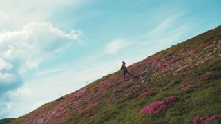 Rotation view of a young stylish teenage girl walking down the flowered mountain meadow. Fashionable look, stylish bomber and snickers Happy emotions, cheerful mood. Feeling free