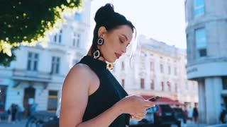 Rotation view of gorgeous stylish young woman surfing the internet via smartphone while standing in the crowded historical city center, looks around, corrects hair and texts back in a bright sunlight.