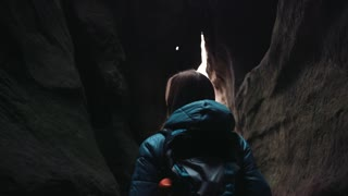 Scared young blonde woman with a backpack walking lost in the dark cave. Dangerous adventure, hiking. Amazing nature.