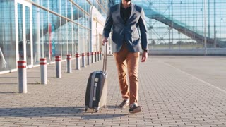 Self-confident handsome bearded man in fashionable suit pulling the suitcase to the airport terminal. Business trip, successful lifestyle. Business appointment, being a boss.