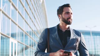 Self-confident handsome bearded man in fashionable suit walking by the airport entrance, using his cellphone and smiling to someone. Being happy, playful mood. Successful lifestyle.