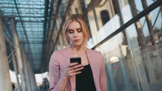 Self-confident hot young blonde girl walks by the business centre, uses her cell phone. Stylish look, elegant white blouse, tight red skirt and leather jacket. Modern lifestyle, businesswoman.