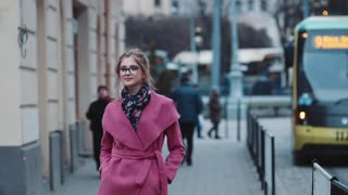 Self-confident young woman in an elegant outfit walking alone down the crowded street. Stylish look, cool haircut and glasses, pink coat. Public transport, citizens on the background.